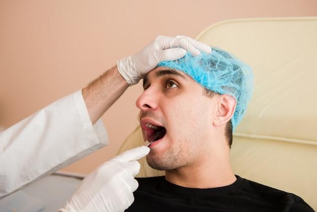 ヘラで患者の口を調べる医師
