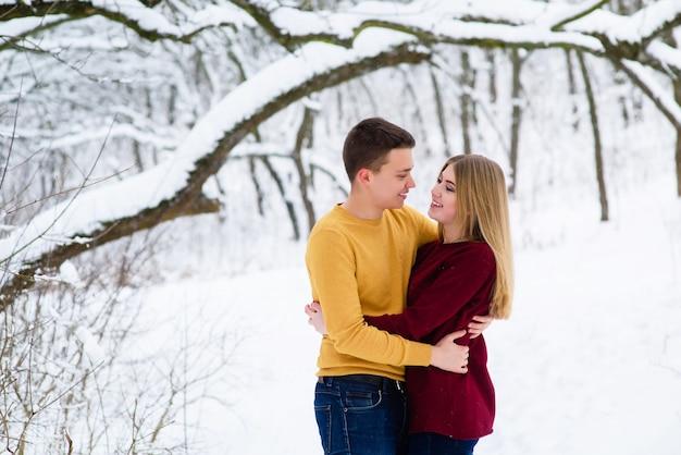 Молодая пара обнимается в зимнем лесу