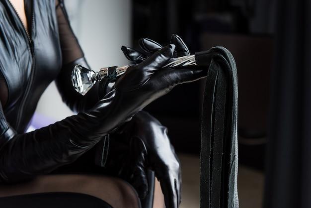Женская рука держит красивый кнут крупным планом
