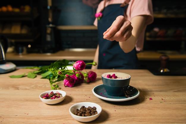 Молодой бариста делает кофе из розового рафа