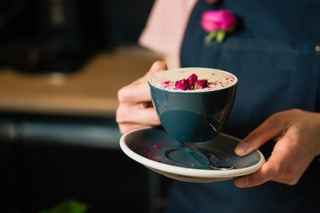 Чашка раф розового кофе в руках бариста