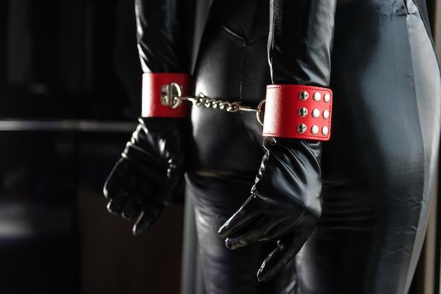 Тело женщины со спины и красные наручники