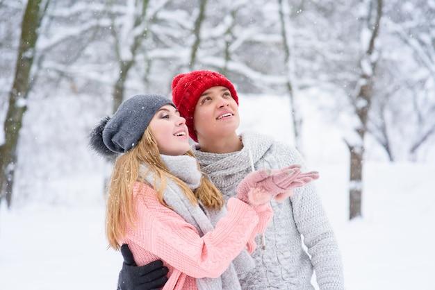 美しいカップル屋外で雪をキャッチ