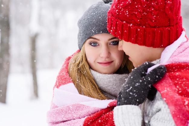 Девушка с голубыми глазами в объятиях своего парня, глядя на камеру