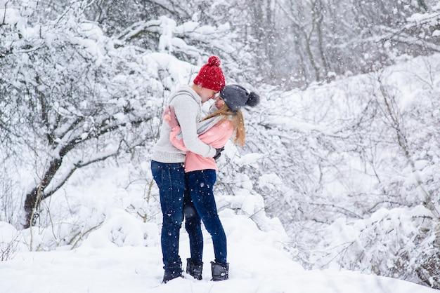 Пара в вязаных шапках собирается поцеловать