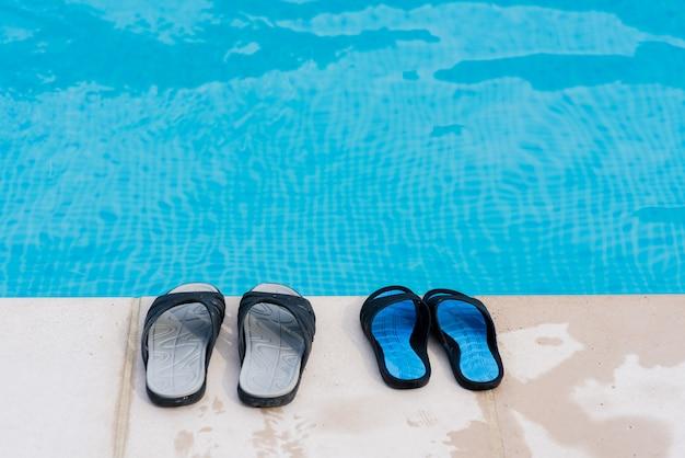 プール近くのビーチサンダルのカップル