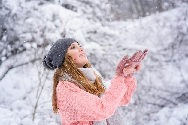 ブロンディの女の子は冬の森で雪をキャッチします。