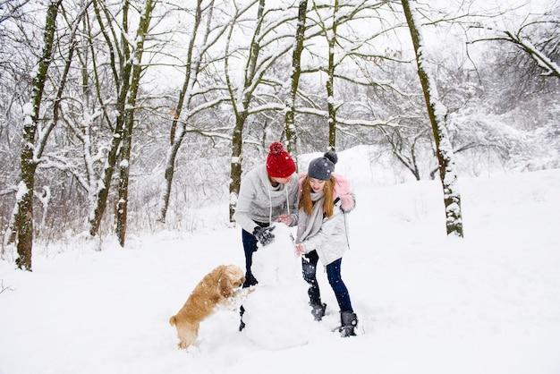Пара делает снеговика с собакой в зимнем лесу