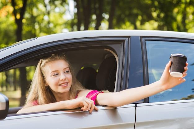 Женщина с чашкой кофе в машине