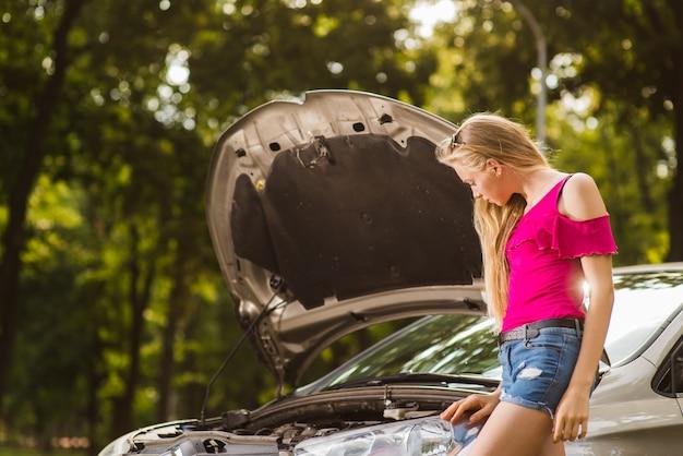 開いている車の近くのブロンディ悲しい女性