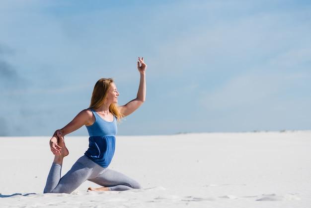 Женщина в позе голубя на дюнах