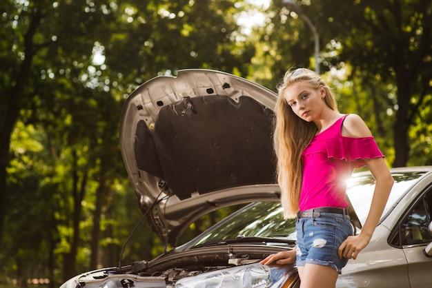 壊れた車の近くの物思いにふける女性