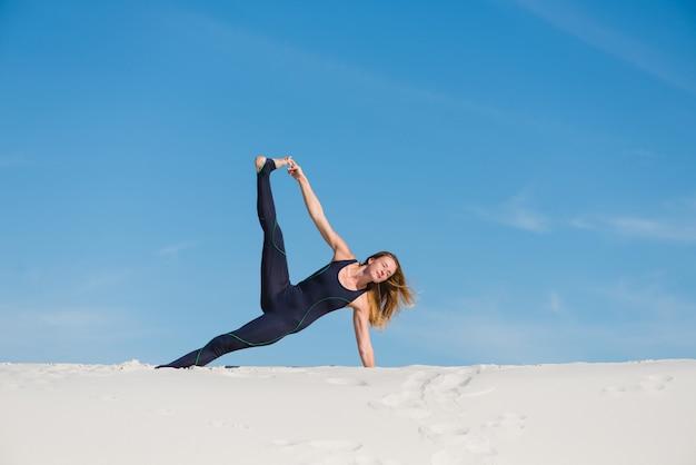 Женщина делает положение морской звезды на открытом воздухе
