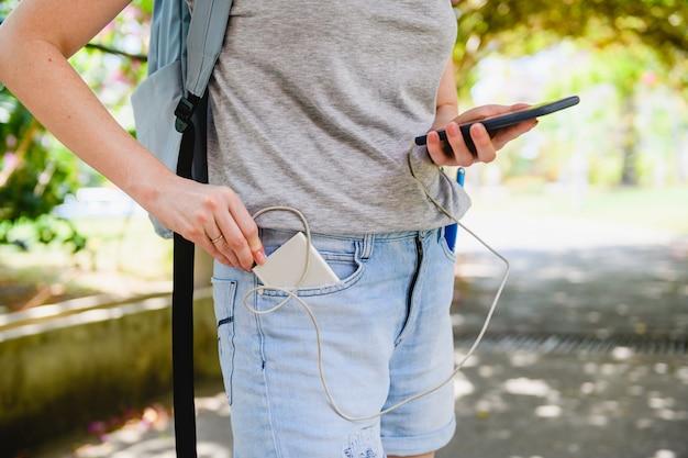 女性観光客がスマートフォンを電源銀行に接続