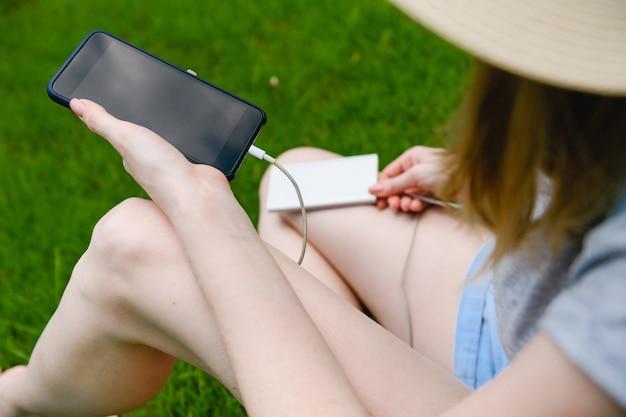 女性はスマートフォンを屋外の電源銀行に接続します