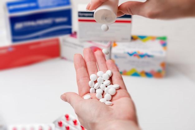女性の手に白い錠剤