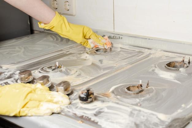 Руки в желтых перчатках моют газовую плиту.