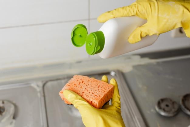 Выдавливание моющего средства на губку, крупный план.