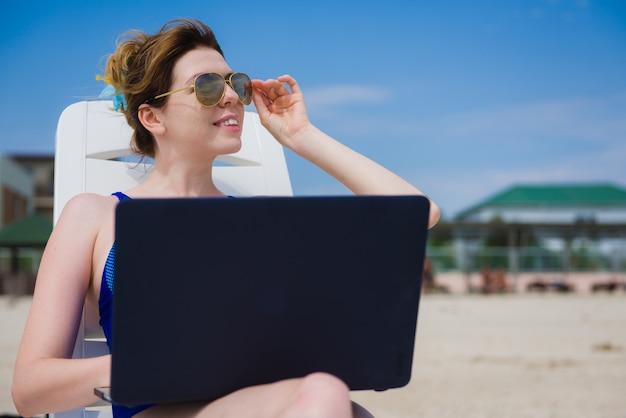 Женщина с ноутбуком на пляже