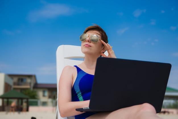 ビーチでラップトップを持つ女性