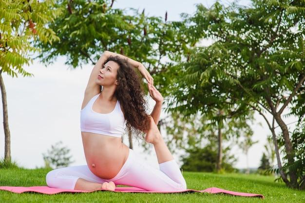 Молодая беременная женщина занимается йогой на открытом воздухе