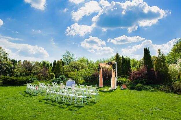 Белые стулья перед красивой свадебной аркой