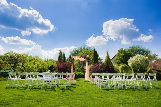 Свадебные арки и белые стулья на фоне природы
