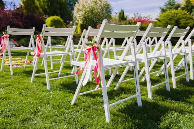 Белые стулья с розовыми и персиковыми лентами