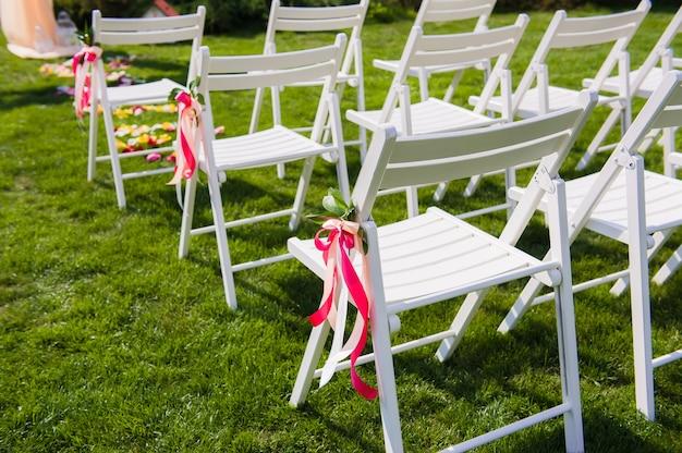 Белые стулья для гостей свадебной церемонии