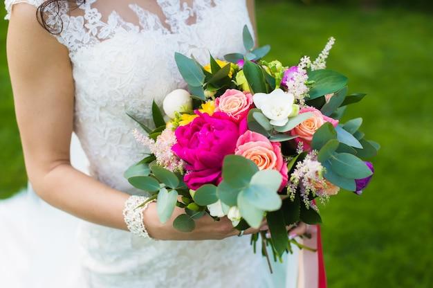 ブレスレットと白いレースのドレスで美しい花嫁