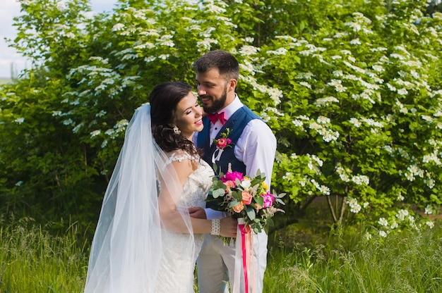 幸せな結婚されていたカップルが緑豊かな庭園でキス
