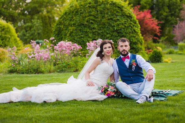 結婚式の日に公園の芝生の上に座って美しい夫婦