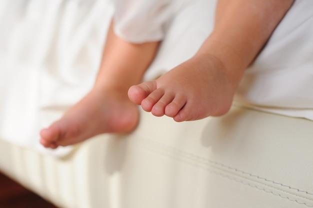 Детские босые ноги, сидя на кровати