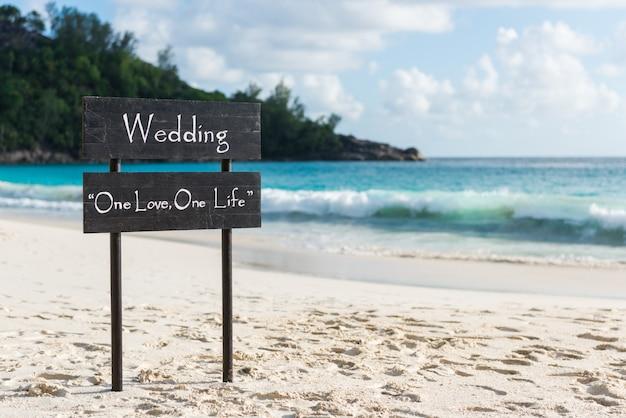ビーチでの結婚式のサインと黒の木製プレート