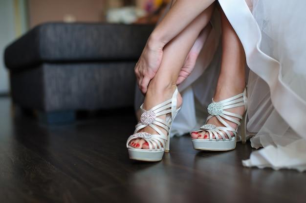 花嫁は結婚式のための白い靴を履く