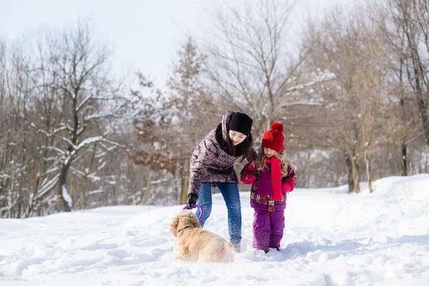 雪の森で犬と遊ぶ母と娘