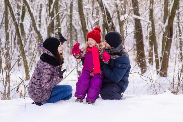 Счастливая молодая семья в зимнем лесу