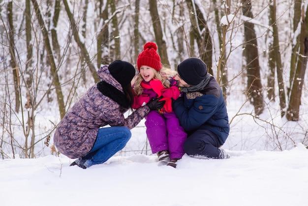 Счастливая молодая семья зимой на открытом воздухе