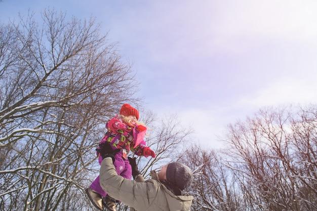 Отец поймать дочь на фоне неба зимой