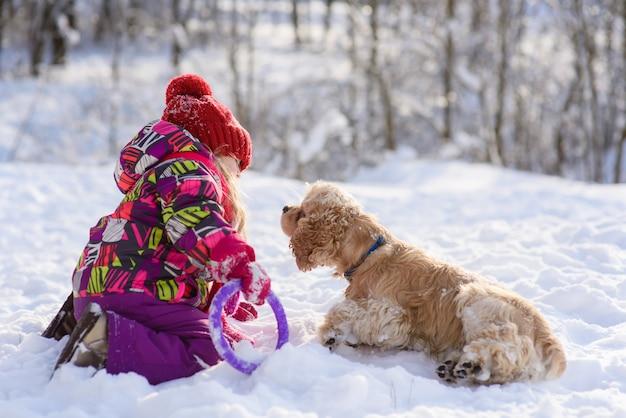 Маленькая девочка, играя с кокер-спаниель в снегу на открытом воздухе