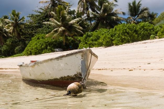 島のビーチでロープを使って古いボート