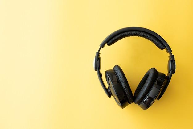黄色の背景に黒の音楽ヘッドフォン