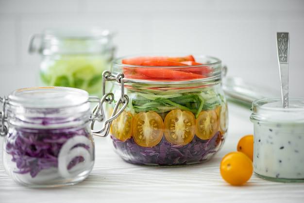 瓶にトマト、キャベツ、キュウリの野菜サラダ
