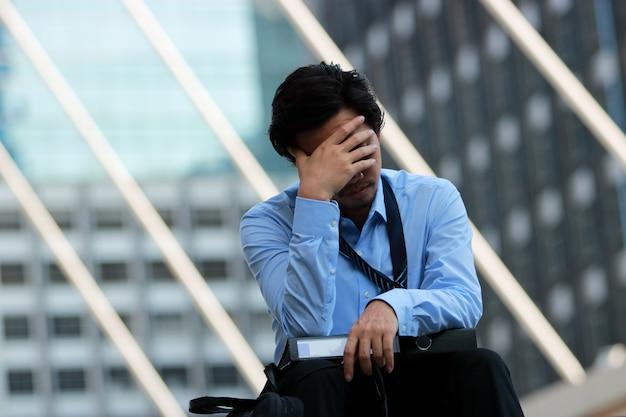 Закрыть безработный молодой азиатский рабочий с руки на лице разочарованы