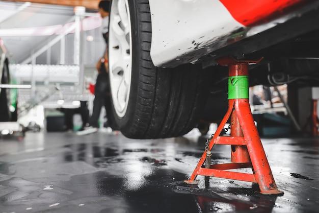 ガレージでタイヤを変えるために車をジャッキアップする。