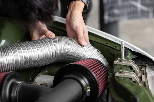 ガレージで車のエンジンを修理する自動車整備士の手