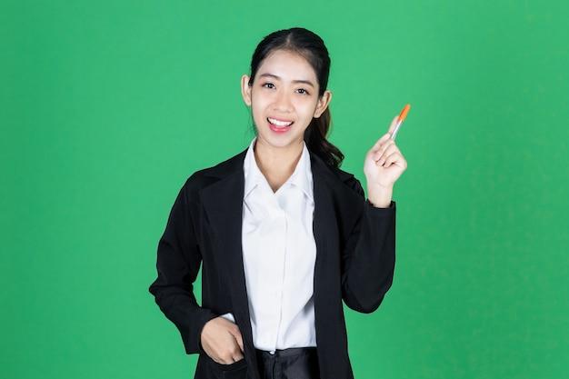 Портрет привлекательной молодой азиатской ручки удерживания коммерсантки и идея иметь