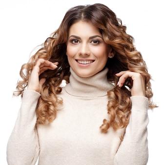Красивая молодая женщина в вязаной шерстяной свитер улыбается