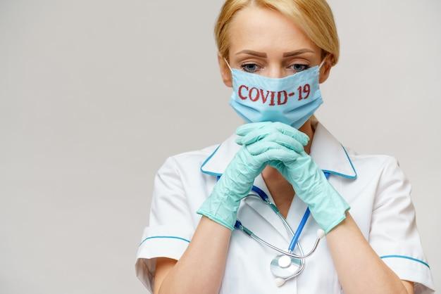 Женщина-врач в защитной маске и латексных перчатках молится и надеется на жест