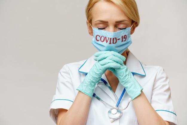Женщина-врач в защитной маске и латексных перчатках молится над надеждой на жест